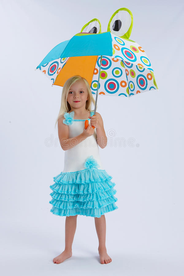 Girl with frog umbrella. Cute young blond girl under open umbrella with pair of frogs eyes; white studio background royalty free stock images