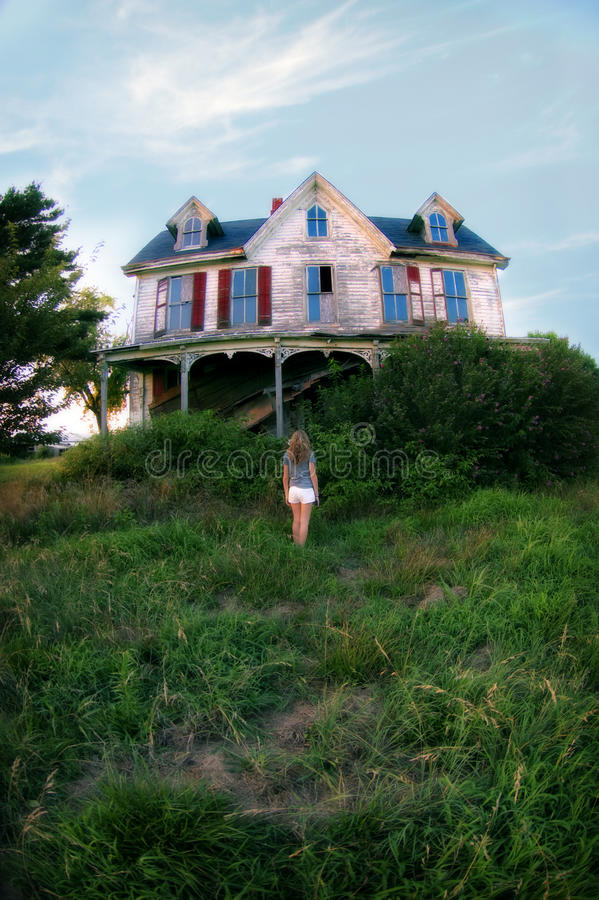 Girl in front of Abandoned house. A back view of teenage girl standing looking at an abandoned, haunted house stock image