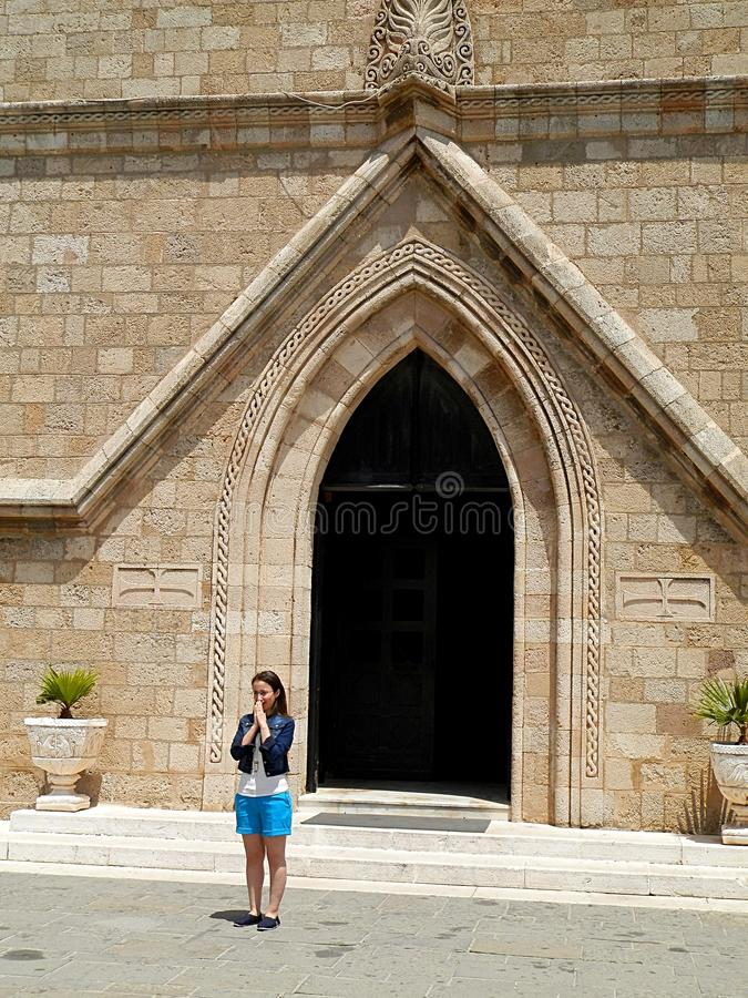 Young woman in front of a church gate royalty free stock photography