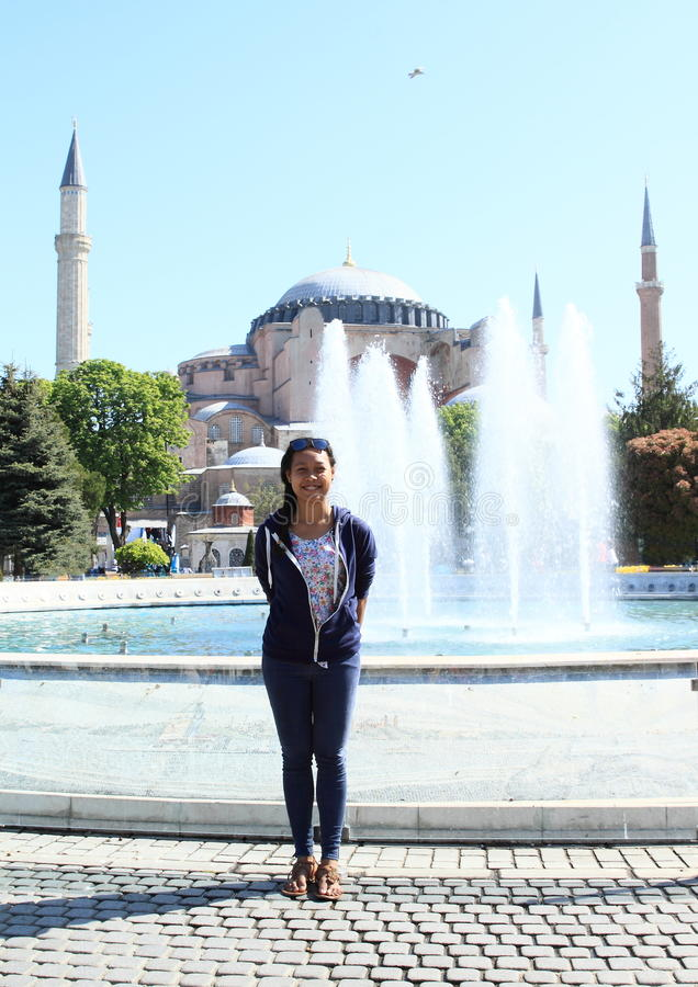 Girl in front of Hagia Sofia in Istanbul. Papuan girl - young tourist woman standing in front of water fountain in Sultanahmed Arkeolojik Park with former church royalty free stock photos