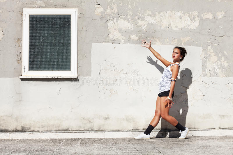 Girl in front of and old wall pointing a window with one arm royalty free stock photography