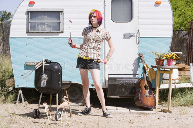 Girl in front of a trailer. With a hotdog and a barbecue stock image