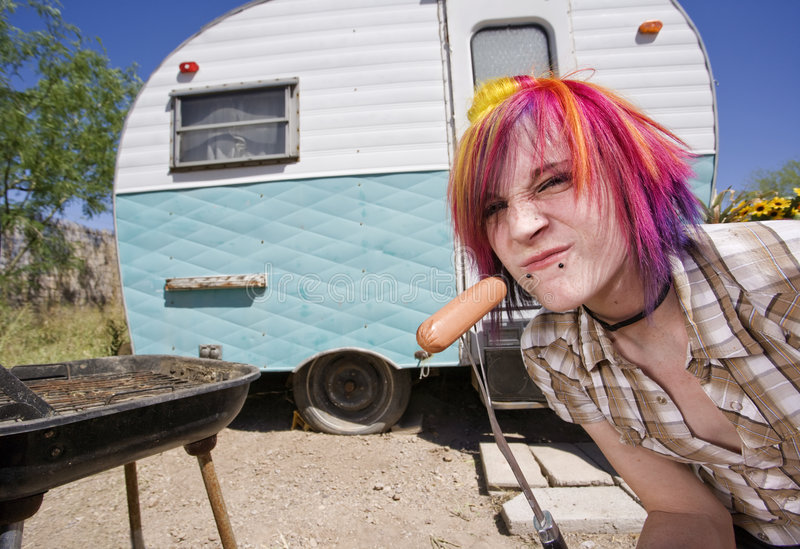 Girl in front of a trailer eating a hotdog. Girl in front of a trailer with a hotdog and a barbecue royalty free stock photo