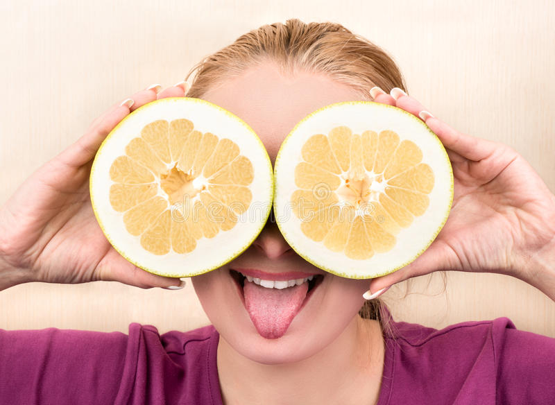 Girl with fruit halves Oroblanco royalty free stock images