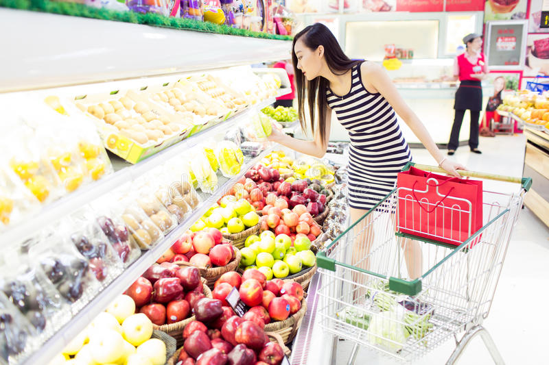 Girl fruit in the supermarket. Beautiful chinese girl, in the shopping center supermarket, buy her favorite fruits and vegetables royalty free stock photos
