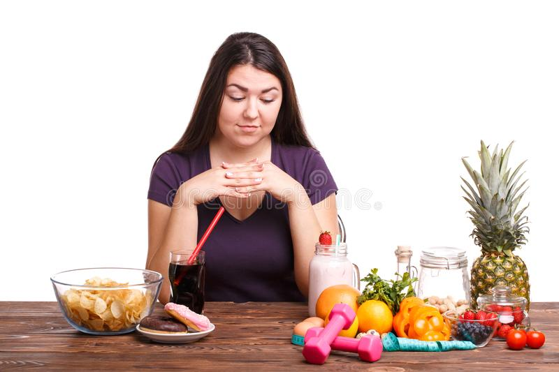 Girl with fruit on the table on a white isolated background royalty free stock photo