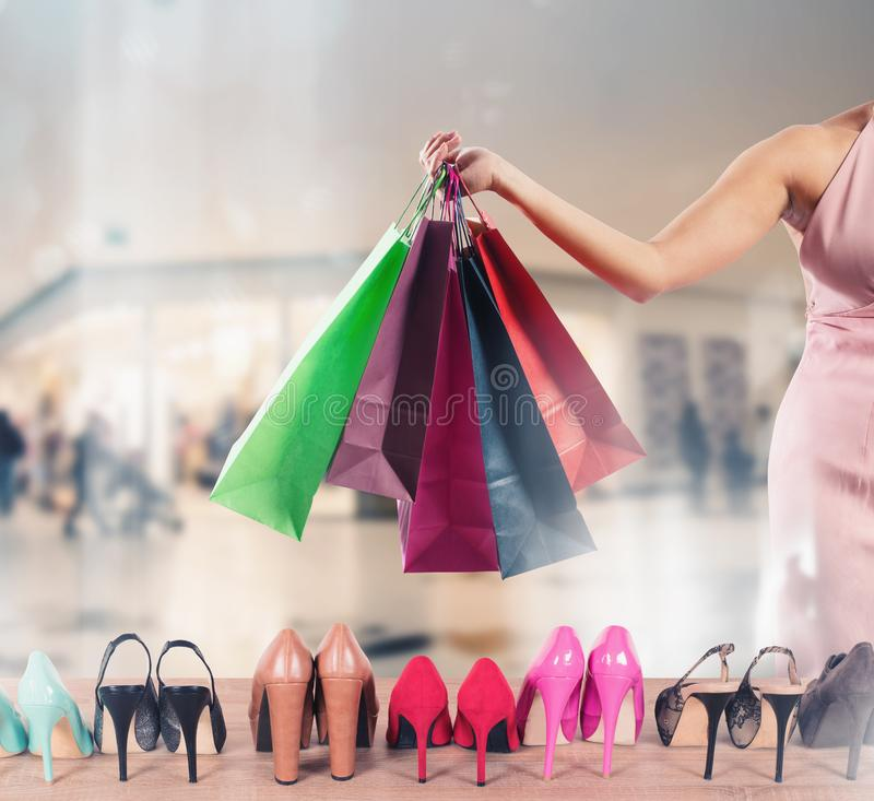 Girl full of bags does shopping in a store stock images