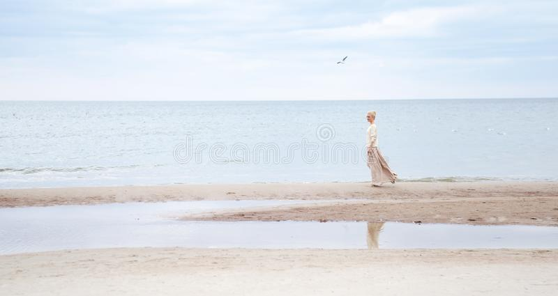 The girl in full growth stands on the beach, ocean. A blond woman in a long beige skirt and a warm white light walks along the coa royalty free stock photos