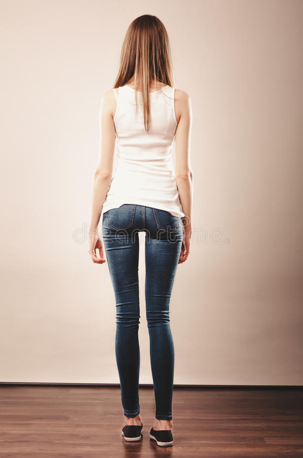 Girl full length in denim trousers white blank top rear view royalty free stock images