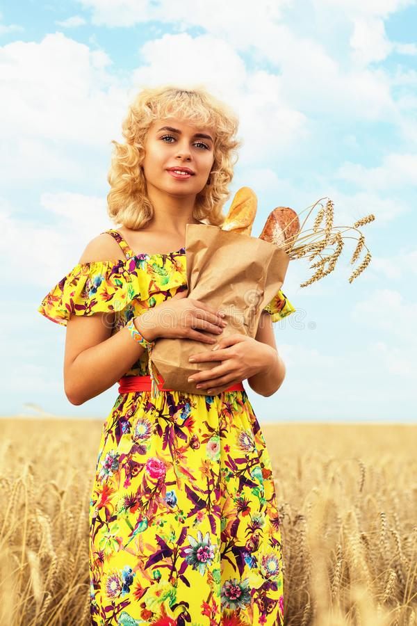 Girl with a full pack of bread in a field with ripe wheat. Model posing on the background of crops ready for harvest. Girl with a full pack of bread in a field stock image