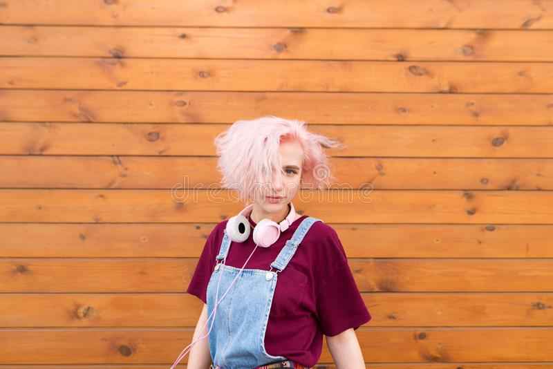 girl with a fun pink hairstyle, headphone and stylish clothes on the background of a wooden wall royalty free stock photo