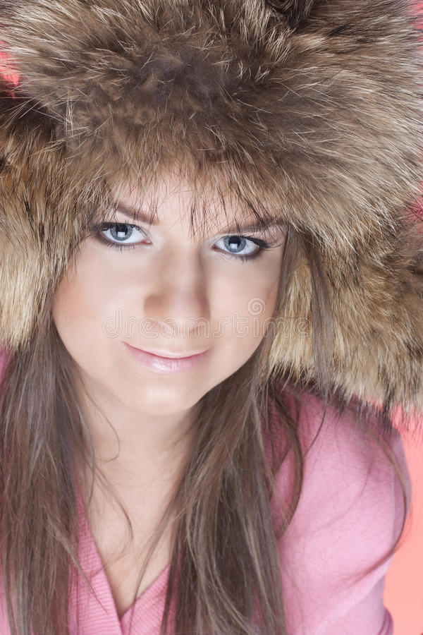 Girl in a fur cap. Portrait of young girls in a fur cap on a pink background royalty free stock images