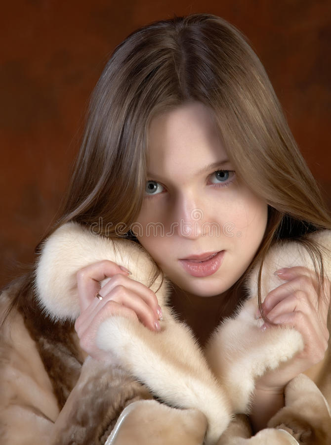 The Girl In A Fur Coat On Motley Background Stock Photo