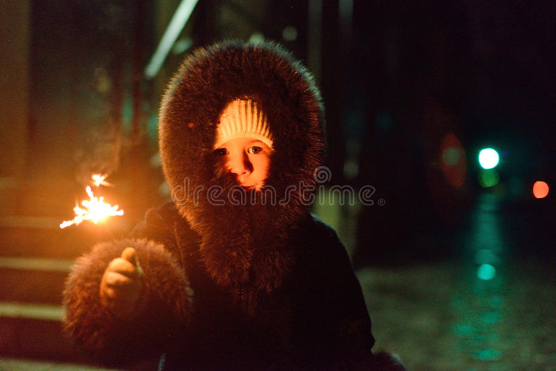 girl in a fur coat with a sparkler in hand stock photo
