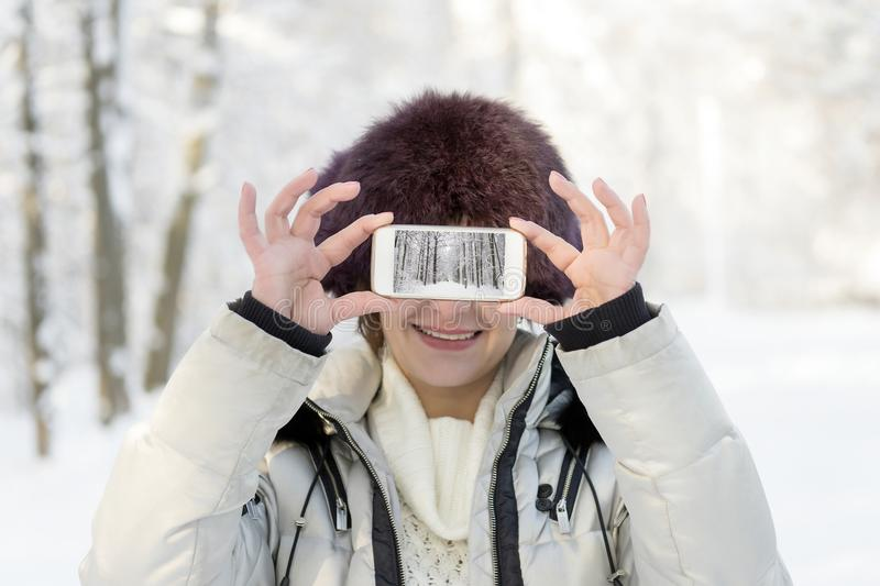 The girl in the fur hat is holding the phone at eye level. On th. E screen, the landscape is telephoned. Winter, day stock photo