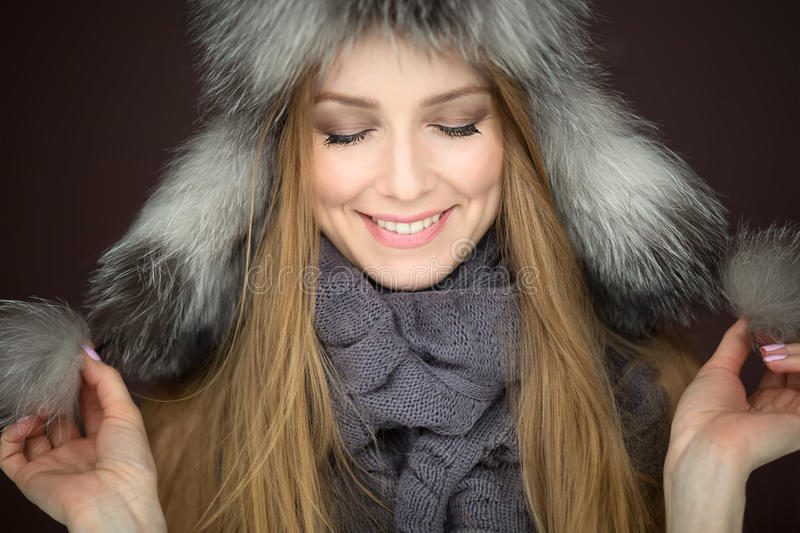 Girl in a fur hat. Smiling royalty free stock photo