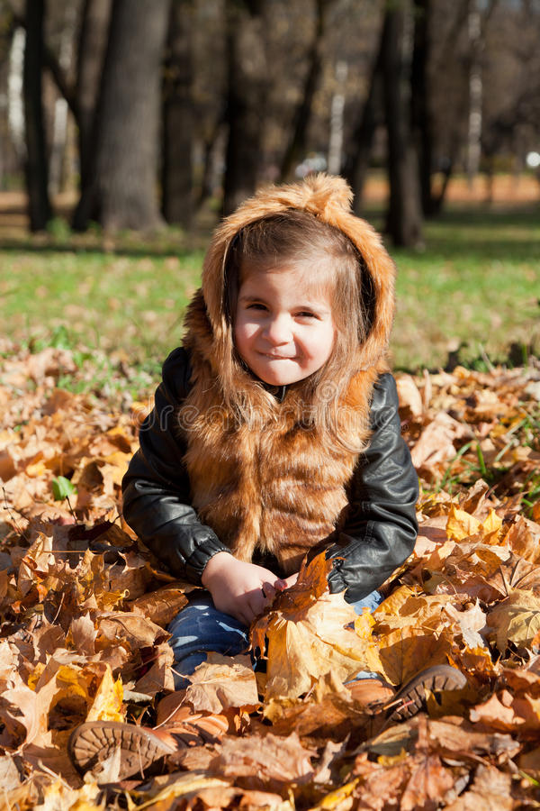 Girl in a fur jacket sits royalty free stock photos