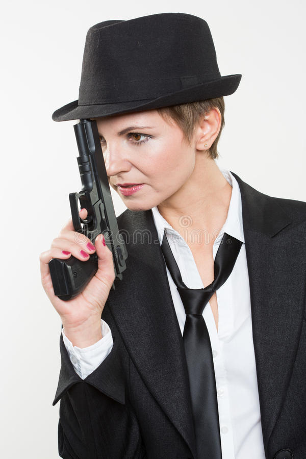 Girl gangster holding a gun. Classic suit and hat. Beautiful girl gangster holding a gun. Classic suit and hat. isolated on white background. red nail polish stock photos