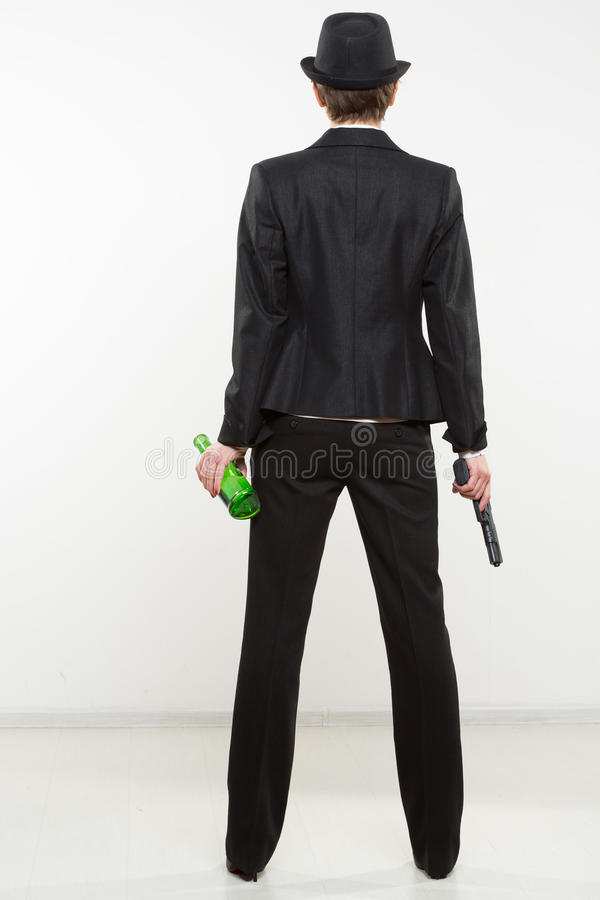 Girl gangster holding a gun. Classic suit and hat. Beautiful girl gangster holding a gun. Classic suit and hat. isolated on white background. red nail polish stock photo