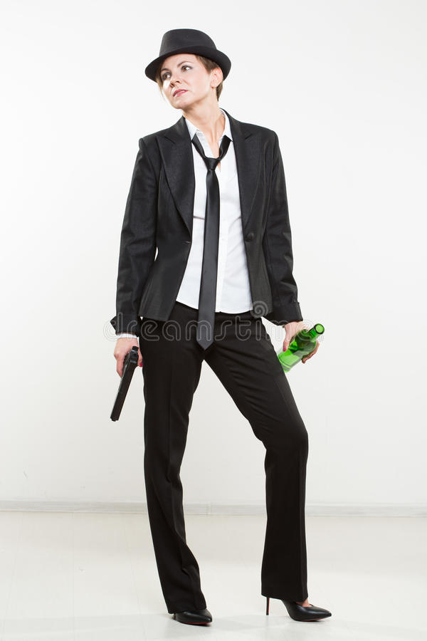 Girl gangster holding a gun. Classic suit and hat. Beautiful girl gangster holding a gun. Classic suit and hat. isolated on white background. red nail polish stock images