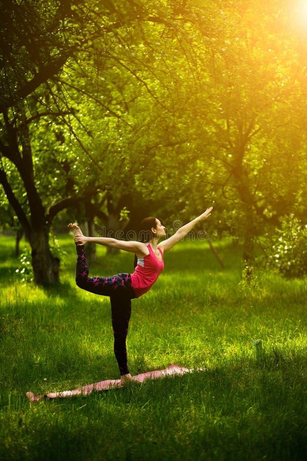 Yoga Training. Girl In Garden Doing Standing Half Bow Pose. Woman  Concentrating While Doing Utthita Ardha Dhanurasana Yoga Pose. Toned Image.