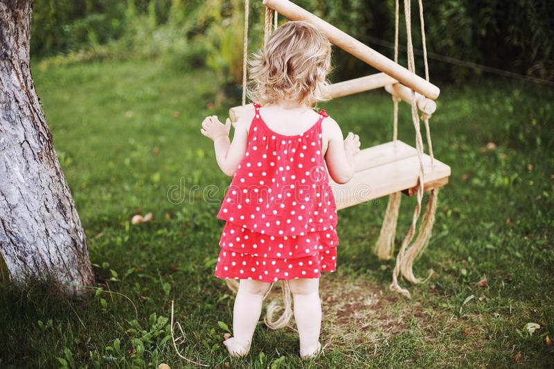 Girl in the garden playing with swings. baby playing in the garden stock photos