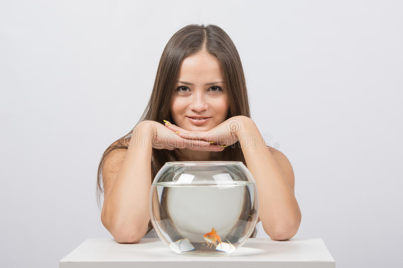 The girl gave the aquarium with goldfish. A young girl sits next to a round aquarium in which swimming goldfish royalty free stock photography