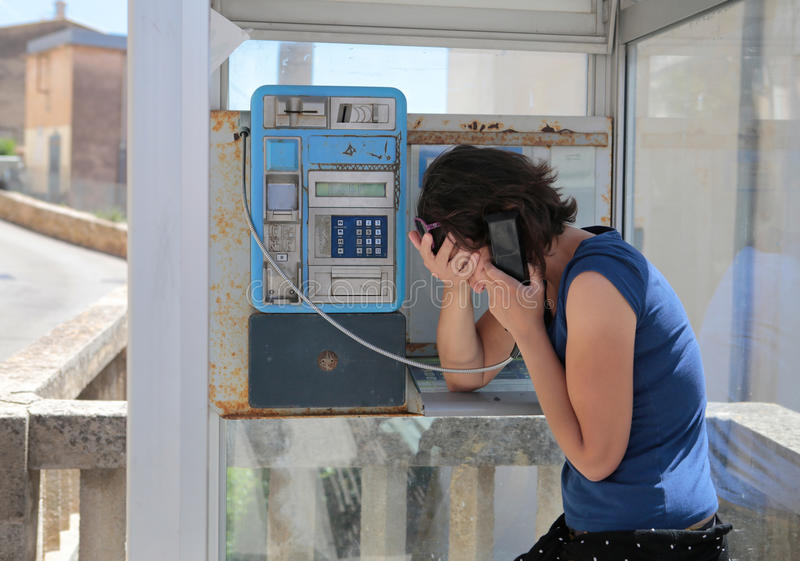 Girl gesturing sad on a phone cabin stock images
