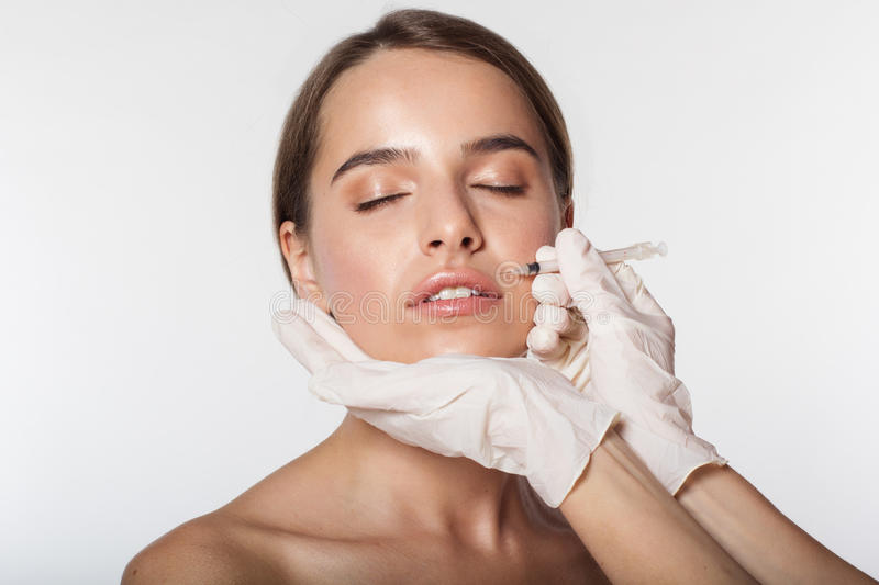 Girl getting beauty injection by doctor. Young woman getting beauty injection by doctor in white gloves isolated on white royalty free stock photography