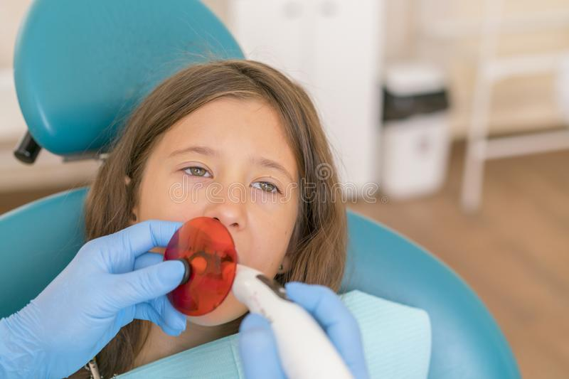 Girl getting dental filling treatment at molar tooth with ultraviolet technology. Image of little girl having her teeth checked by. Doctor stock image
