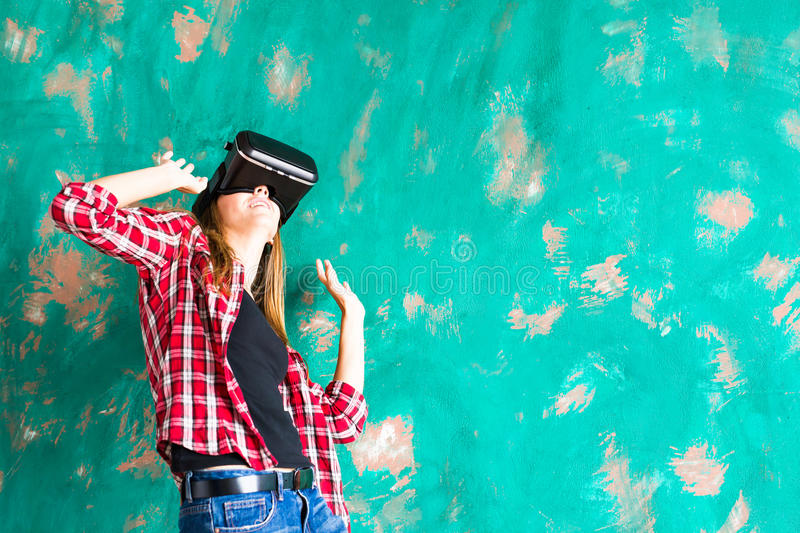 Girl getting experience using VR-headset glasses of virtual reality gesticulating hands royalty free stock photos