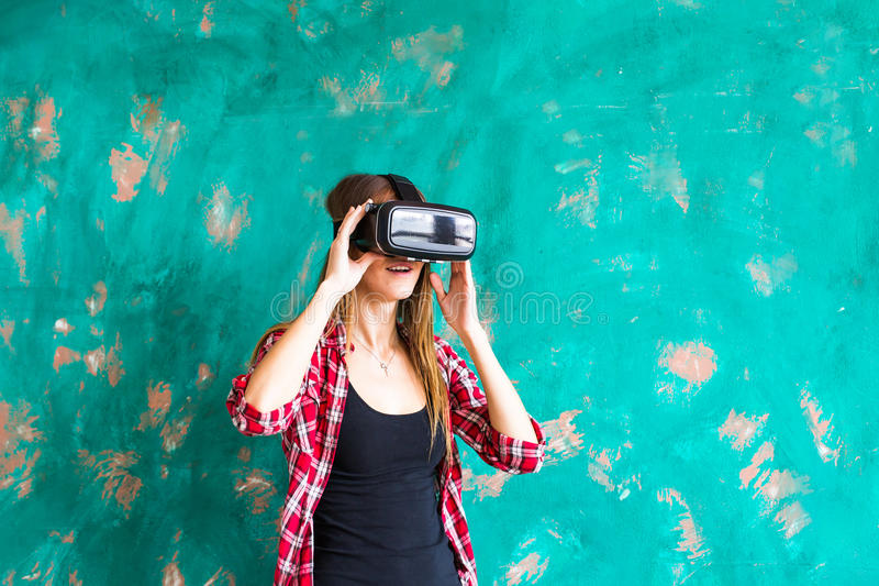 Girl getting experience using VR-headset glasses of virtual reality gesticulating hands stock photo