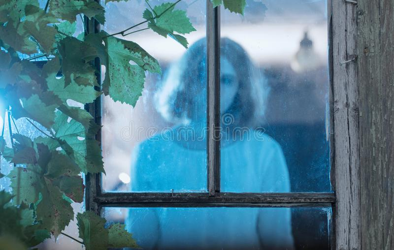 Girl ghost in the old window. The girl ghost in the old window stock photo