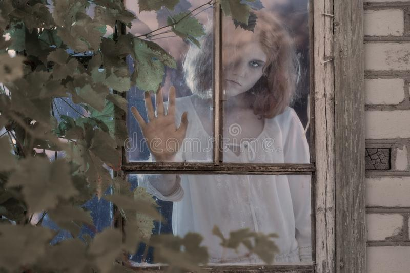 Girl ghost in the old window. Scary girl ghost in the old window stock image