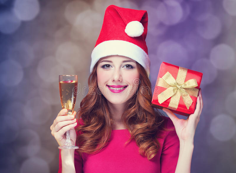Girl with gift and champagne. Redhead girl in christmas hat with gift and champagne royalty free stock photos