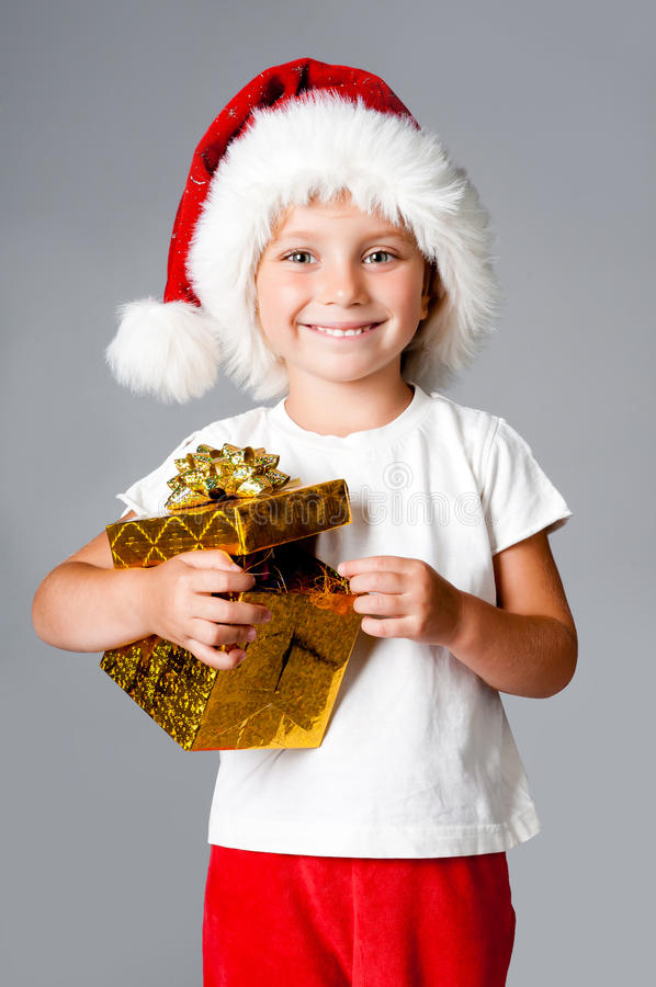 Girl with gifts in santa hat. Beautiful little girl with gifts in santa hat royalty free stock photos