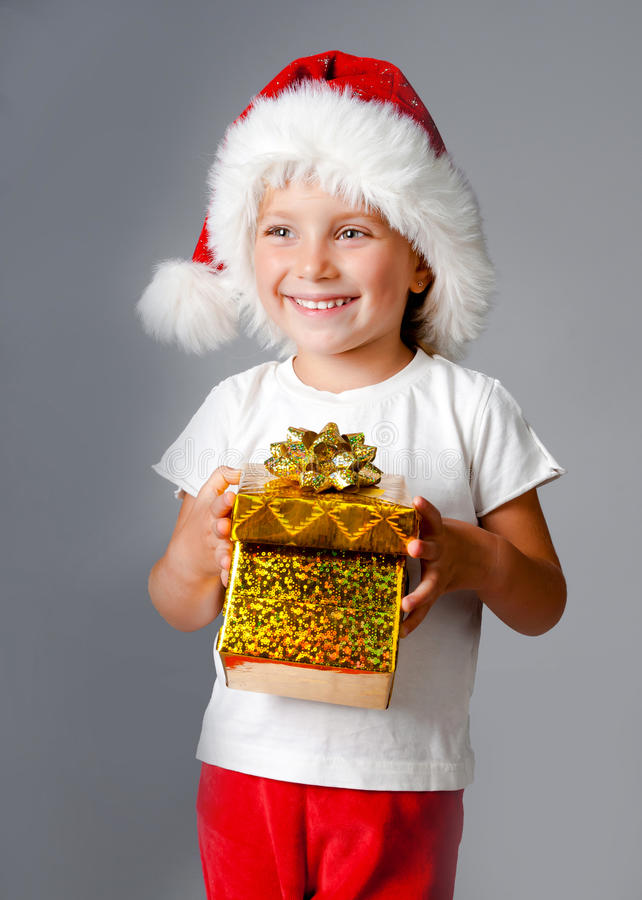 Girl with gifts in santa hat. Beautiful little girl with gifts in santa hat stock photography