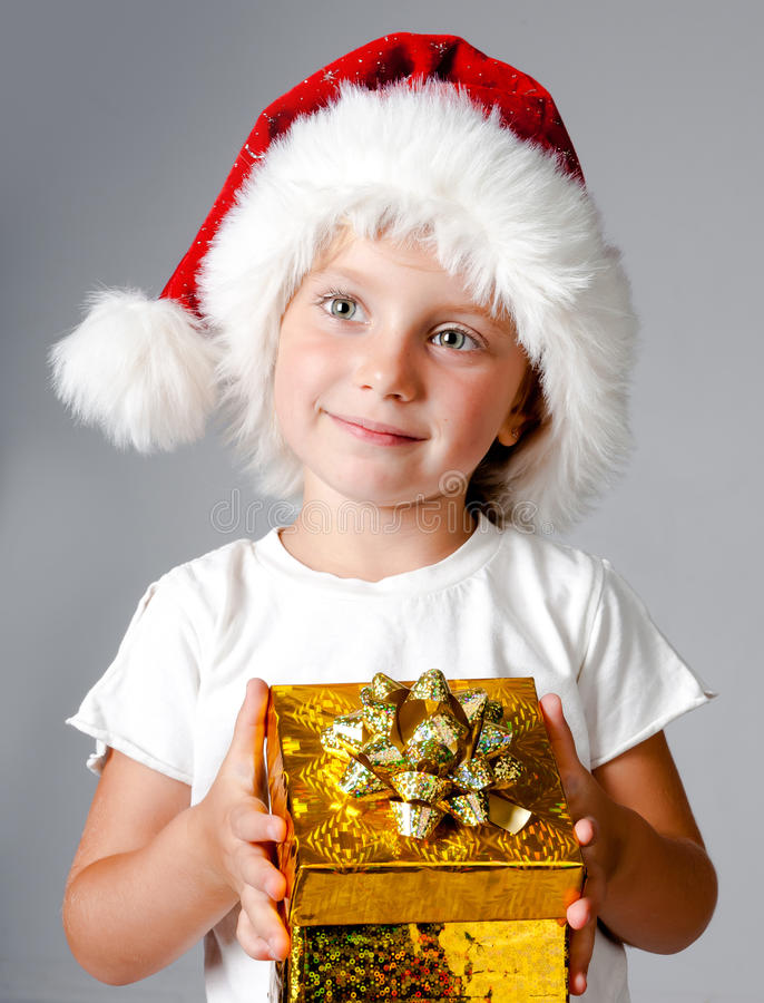 Girl with gifts in santa hat. Beautiful little girl with gifts in santa hat royalty free stock photo