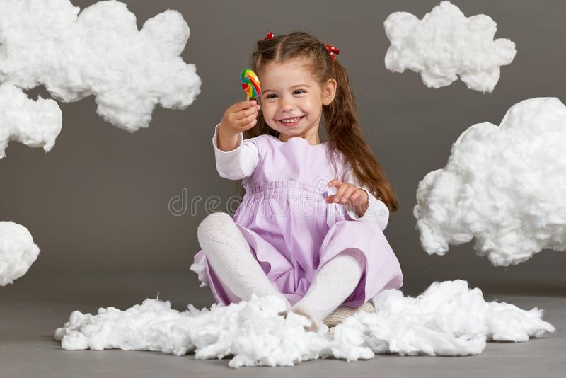 Girl girl eating candy and playing with clouds, shooting in the studio on a gray background, happy childhood concept royalty free stock image