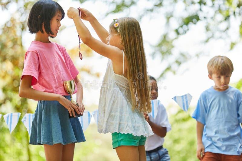 Girl gives the winner a medal. In kindergarten stock photos