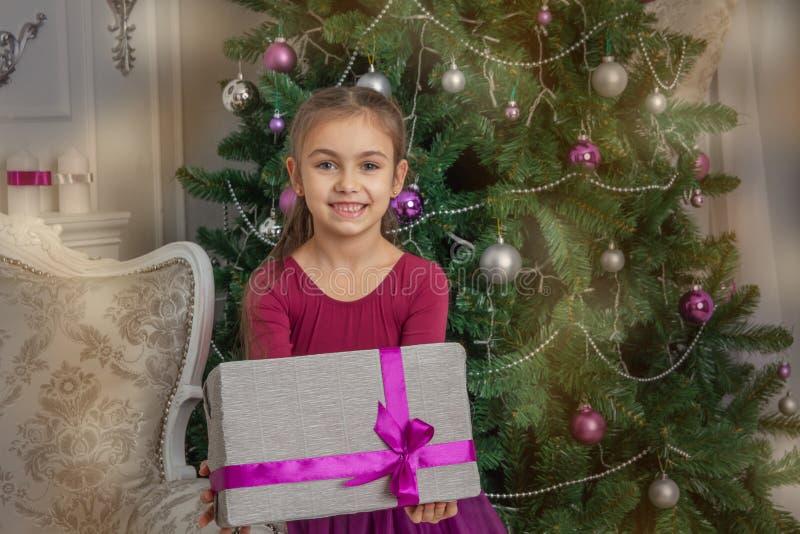 Girl giving gift under Christmas tree stock photo