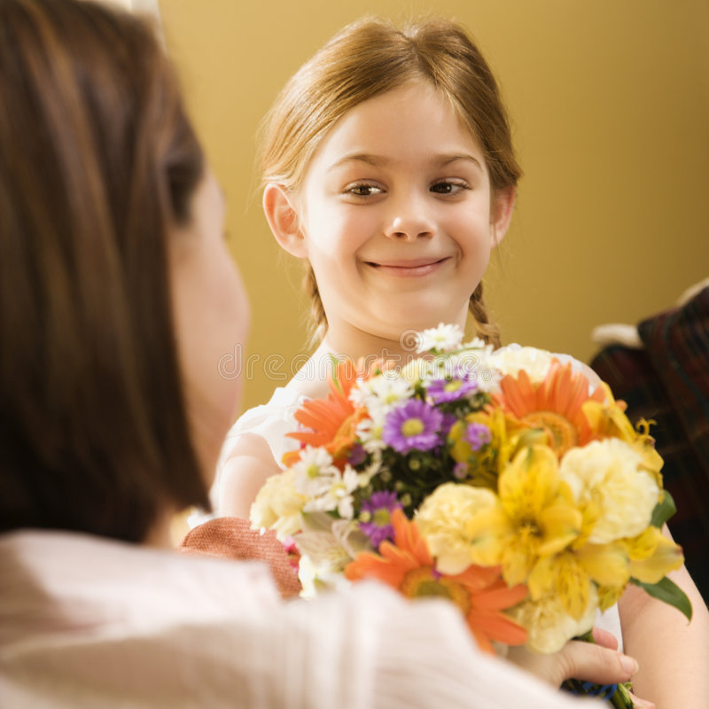 Girl giving mom flowers. stock photography