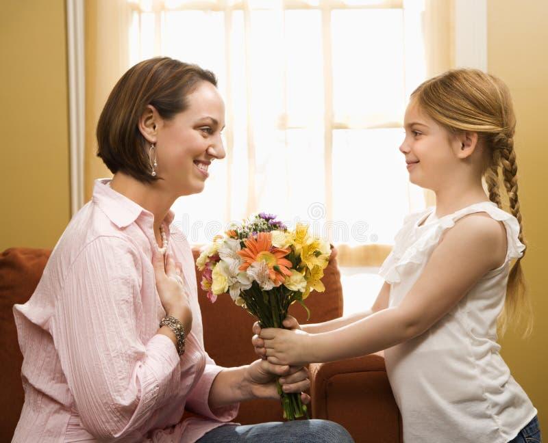 Girl giving mom flowers. stock images