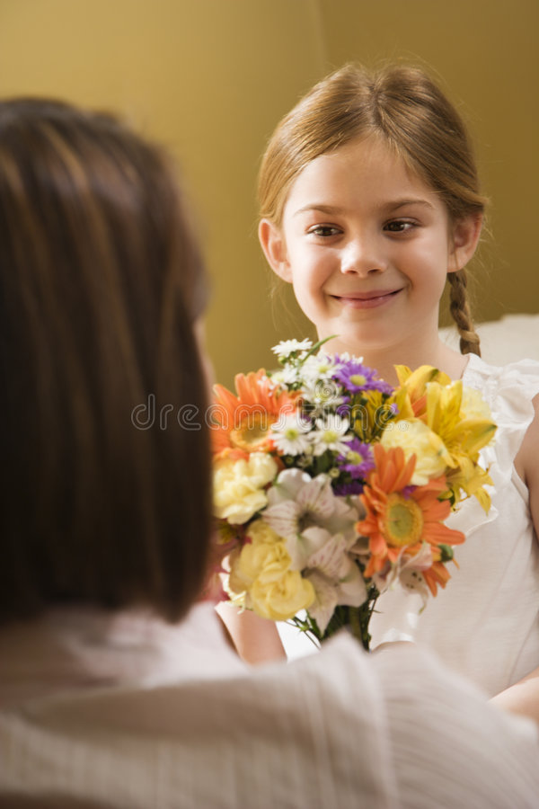 Girl giving mom flowers. royalty free stock photo