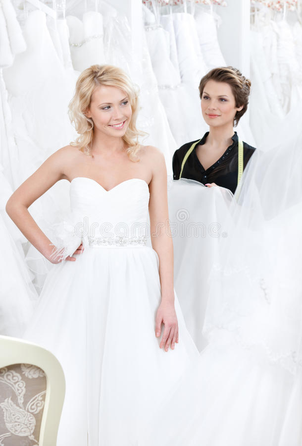 Girl is glad to put on this wedding dress stock images