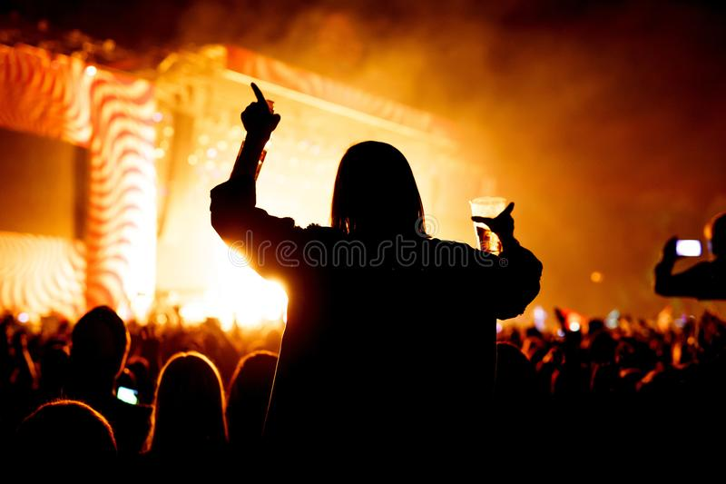 Girl with glass of beer enjoying the music festival, concert royalty free stock image