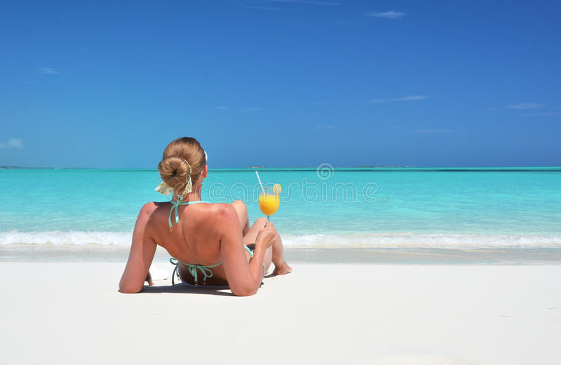 Girl with a glass of orange on the beach stock photos