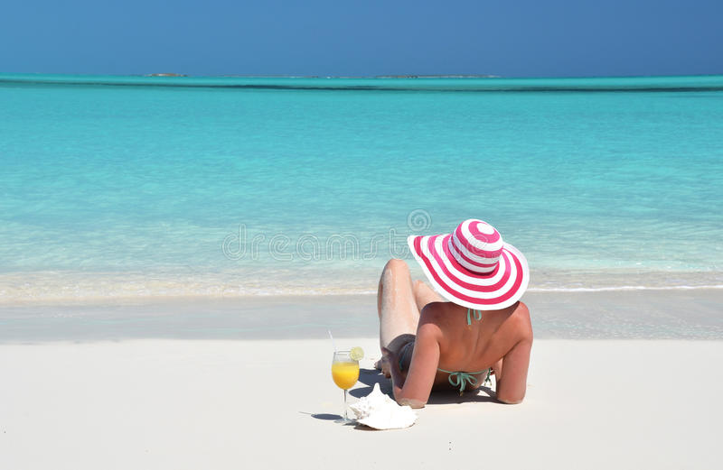 Girl with a glass of orange juice on the beach stock photos