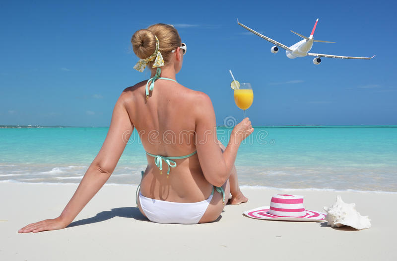 Girl with a glass of orange juice on the beach stock images