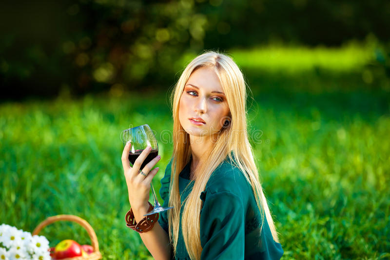 Girl on the grass with a glass of wine royalty free stock images
